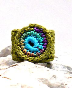 """This is a handmade fine thread crocheted ring in peacock colors on a light olive band. The band is approximately ¾"""" (1.5 cm) wide and 2 1/2 """""""