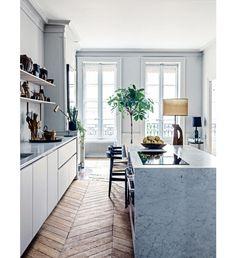 White kitchen with wood herringbone floors marble waterfall island