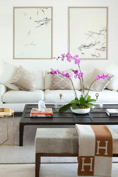 Chic living room boasts a pair of abstract art pieces placed above a white sofa adorned with gray velvet pillows facing a large black low coffee table and a round brass accent table, Gaultier Side Table, as well as gray cowhide bench draped in a Hermes Avalon Blanket.