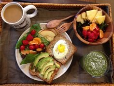 healthy brunch - avocado & egg sandwich with green smoothie and fruit bowl