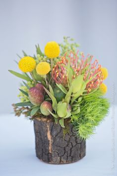 A rustic wood container with yellow billy balls, orange pincushion protea. An Aspen Branch Original. www.aspenbranch.com