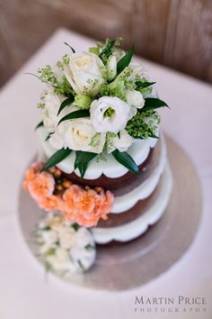 Wedding cake with white and orange flowers. By Martin Price Photography www.martinpricephotography.co.uk