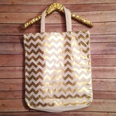 "NWT Gold & White Chevron Canvas Tote Bag This is a gorgeous NWT Gold and White Chevron Canvas Tote Bag. Gold and white chevron on one side and gold paint splatter on other side. White canvas handles 21"" length. Tote length 17"", width 16"", bottom depth 3.5"". Bags Totes"