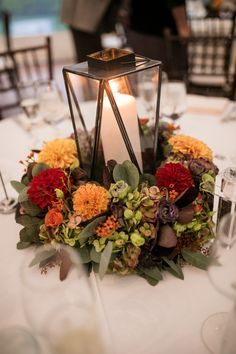 Fall reception centerpiece with red, orange, and yellow flowers, greenery, and black lantern with candle. Willowdale Estate, a weddings and events venue in Topsfield, Massachusetts. WillowdaleEstate.com | Dan Aguirre Photography