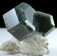 Two dark green Apatite crystals on lighter colored Apatite matrix.Apatite is a group of phosphate minerals, usually referring to hydroxylapatite, fluorapatite and chlorapatite, named for high concentrations of OH−, F−, Cl− or ions, respectively, in the crystal. The dark crystals are hexagonal crystal form with beveled edge faces all around, and has lustrous surfaces throughout. Collected August 2007. Locality Sapo Mine, Goiabeira, Minas Gerais, Brazil Dimensions 20 x 20 x 15 mm.