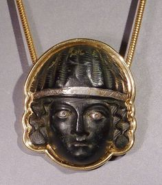 Early Roman bronze applique head of a woman with silver eyes and diadem, set in modern 18k gold setting.      1st century BC – 1st century AD.