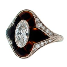 Stunning Art Deco cocktail ring by Tiffany & Co., 1910's. Features an approx 0.76-ct marquise cut diamond framed with pre-cut horn and accented with single cut diamonds set in platinum.