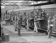 "THE BRITISH ARMY IN THE UK: EVACUATION FROM DUNKIRK, MAY-JUNE 1940  part of ""WAR OFFICE SECOND WORLD WAR OFFICIAL COLLECTION"" (photographs) Made by: Saidman (Mr)  Refreshments being served to evacuated troops aboard a train at Addison Road station, London, 31 May 1940."