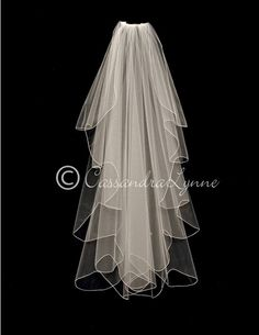 The cut of this waltz length veil give it a full waterfall look. The edge is scalloped and embroidered. It is 48 inches long and 72 inches wide, on a four inch