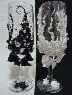 Par de taças em vidro, decorada em pedraria e flores de biscuit. <br>Noiva branca e noivo Preto. <br>Sobre cores e outros modelos consulte-nos.