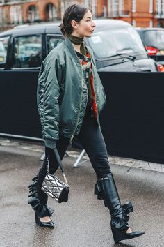 Irina Lekicevic wearing a green oversized bomber jacket with black jeans, black frilled knee-high boots and a silk scarf.