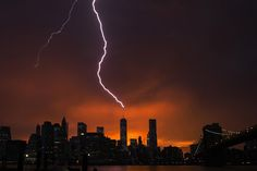 Image 21 of 24: Lightning strikes One World Trade Center in Manhattan as the sun sets behind the city after a summer storm in New York July 2, 2014. REUTERS/Lucas Jackson