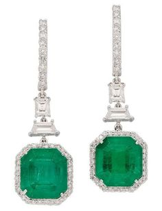 Exquisite Emerald and Diamond Ear Pendants. A pair of octagonal-cut emeralds together weighing approximately 13.90 carats, each framed by a border of small round diamonds, and suspended from trapezoid-cut and rectangular diamonds topped by a surmount decorated with a line of round diamonds, mounted in 18k white gold, all that glitters is not gold, sometimes it's diamond's & emerald's.