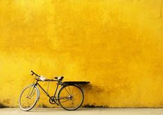 Unattended bicycle leaning on yellow wall in Hoi An, Vietnam... /:/