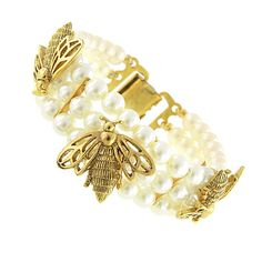 Vintage Couture's antique style triple strand bracelet features simulated costume pearls. The triple strand bracelet has delicately placed gold tone bumblebee embellishments and a fold over clasp. Vintage Couture is nickel-free and made in the USA from premium components.