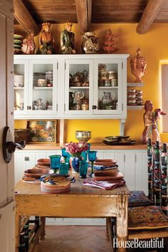 Judith Espinar choose a happy yellow color as a backdrop to the pottery collection she displays in her kitchen, a traditional adobe space that was renovated by Jim DeVille and Scott Robey.