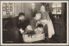 Man, twee vrouwen en een baby in Volendammer streekdracht. De baby ligt in een wieg. De opname is gemaakt in een interieur.