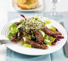 Salat mit Steak: Auf verschiedene Blattsalate betten sich zarte Steakstreifen, eine herrlich würzige Knoblauchsauce und knackige Sprossen.