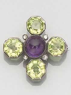 An early 20th century Suffragette brooch. The cross-shaped mount, each arm set with an octagonal-cut peridot, centred by a cabochon-cut amethyst and accented with four rose-cut diamond points, the colours of the stones representing the motto 'Give Women Votes', length 2.5cm.