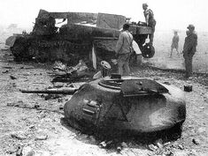 Afrika Korps soldiers inspect the wreckage of a Grant tank, which has been shattered after a violent explosion.
