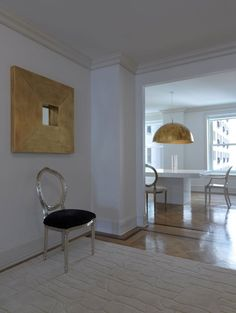 NY Apartment by Teresa Sapey. Total simplicity, in a two-colour symphony of black and white, that dialogs with the view, the world's most breathing cityscape. Conceptual Minimalism and total whiteness, as if we were tiptoeing through the space and then clapping our hands now and again; echo comes in the gilded lamps and mirrors that hark back to an opulent past and serve as a reminder of the building origins, when it was the trendiest hotel in NYC.
