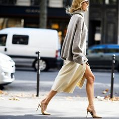 An oversized turtleneck sweater is worn over a pale yellow dress and paired with nude pumps.