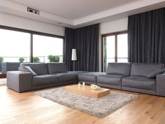 Modern Living Room with Wooden Flooring Idea and L Shaped Leather Grey Sofa Design Near Small Cream Coffee Table feat Grey Fur Carpet Area and Black Curtains Of Windows also Glass Floor Lamp Living Room Hardwood Floors, Grey Walls Living Room, Living Room Carpet, Living Room Sofa, Gray Walls, Living Rooms, Grey Sofa Design, Gray Interior, Interior Design