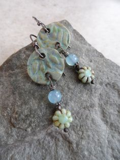 Wonderful, earthy ceramic charms, expertly handcrafted by an etsy artisan, are perfectly paired with artisan-made Czech glass flower headpins with tinwork and genuine AAA Blue Chalcedony beads. Ive added sterling spacers and suspended these pretty earrings from handcrafted solid sterling earwires. Measure 2 1/4 from top of earwires. One-of-a-kind beautiful!  The metalwork on the headpins is called tinwork, which is similar to pewter but is absolutely safe. The compound is for making jewe...