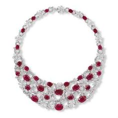 Mounted in 18k white and yellow gold, the bib necklace, designed as an openwork panel of thirty oval-shaped rubies weighing approximately from 7.00 to 1.21 carats, connected by keystone and whistle-cut diamond overlapping circular links, interspersed by pear-shaped diamond florets, accented by brilliant-cut diamonds, extending to the backchain.