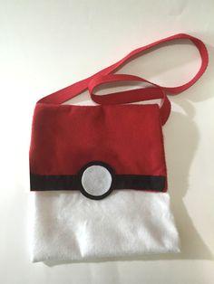 Bolsa inspirada na pokebola, elemento principal do desenho Pokemon. Confeccionada em feltro branco e vermelho, detalhes em preto e fecho em velcro.    **** Todas as bolsas seguem embaladas e com tag personalizada com o nome da aniversariante.  Medidas:  Alça: 75cm  Altura da bolsa: 24cm  Largura ...