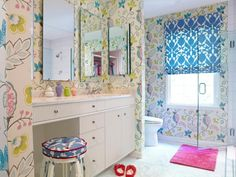 This girls bathroom has a colorful floral wallpaper that gives this space a lively feel. The bright blue patterned window treatments, upholstered stool cushion and the white cabinets round out the room.