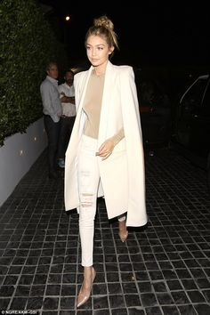 Classy: The 20-year-old finished the outfit with an elegant white coat cloak, and help her long blonde tresses tied up in a rough knot