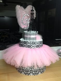 Paris themed diaper cake! Bottom Layer is a hat box from Hobby Lobby. Great way to add height and throw in some extra goodies. Tutu is a high chair decoration purchased in the party aisle at Hobby Lobby as well and it ties perfectly in the back. The little pink puff is a hair clip that baby can use later. Easy, simple and fun!