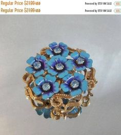 This  #vintage blue rhinestone flower brooch and pendant is gorgeous!!  It features a gold tone setting with a cluster of beautiful blue flowers accented with purple enamel.... #ecochic #etsy #jewelry #jewellery #rhinestones
