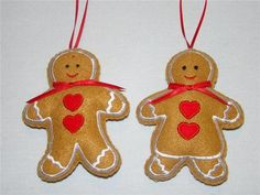 """This adorable hand~crafted Gingerbread Boy and Girl pair are made of felt with an appliqued heart in the center, white embroidered trim and a red satin bow and hanger. They measure approx. 5"""" high."""