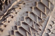 Macro Close Up of Fresh Motorcycle Tread Pattern on Muddy Trail; short suggest adventure, sports, offroad riding, and getting off the beaten track.