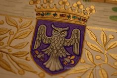 Detail of coat of arms from the border of the illuminated painting The Lady and the Swan by British artist and illuminator Andrew Stewart Jamieson. The shield is 3cms high.
