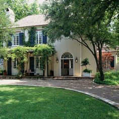 The goal of capturing maximum light guided the design of this home inside and out. On the front of the house, tall, shuttered windows with 20 and 24 panes recall French doors. A majestic pecan tree and leafy pergola filter the light and soften high-summer harshness.