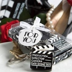As Low As $1.25.  Whether you're having as Oscar party, Hollywood themed wedding, or wish to represent a love for film, Lights, Camera, Action Key Chain can help you enhance your theme and color scheme while sending guests home with a token of remembrance they can have with them wherever they go!