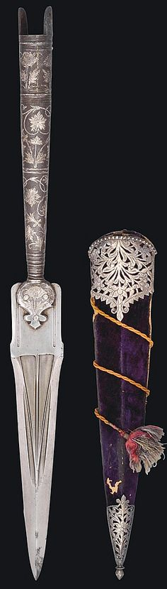 Indian (Mughal) spearhead, 18th century,  heavy triangular watered steel blade deeply carved with central ridges, the steel shaft with silver-overlaid floral decoration, the original purple velvet covered sheath with silver mounts, 21¾in. (55cm.).