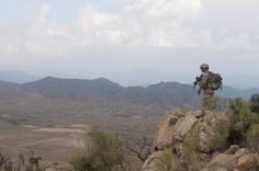 """Sgt. 1st Class James Mastrodomenico from Lake George, N.Y., of C Company, 3rd Battalion, 66th Armor Regiment, Task Force 2-28, 172nd Infantry Brigade, scouts a route down from the summit of a mountain named """"Big Nasty"""" Sept. 7.  He is looking down into Pakistan here."""