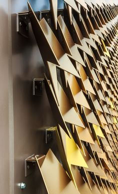 Individual metal clips attach metalic leaf-shaped shingle cladding to the wall at the Mayfair House in London, England by Squire and Partners.