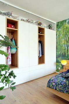 I když této originální ložnici jasně vévodí dřevěná postel Javorina s okrasnou flórou kolem, šatní skříň podél zdi rozhodně také stojí za zmínku. Sestavu tvoří skříně i zásuvky z laminových desek v bílé barvě, uprostřed doplněné o dva výklenky z dubového dřeva. V nich se našlo perfektní místo pro zavěšení oblíbených svršků, zatímco zbytek garderoby je uspořádaný uvnitř. Prosklená vitrína nahoře pak ukrývá úctyhodnou sbírku vesmírných lodí z předaleké galaxie… Closet, Home Decor, Armoire, Decoration Home, Room Decor, Closets, Cupboard, Wardrobes, Home Interior Design