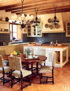 Michael S. Smith Reimagines a Majorcan Estate ~ Custom-made Moorish-style tile enlivens the kitchen, where antique oak dining chairs surround an Indian table; the chandelier is by Paul Ferrante, and the globe lights are by Jamb.