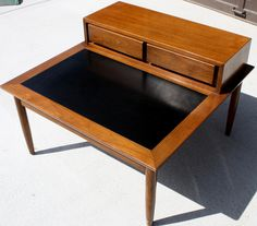 Mid Century Modern Square Coffee Table with Shelf & Drawers - This is a Mid Century Modern square coffee table. It has a solid wood base, the mcm formica tile top, and signature tapered legs. It also has an upraised shelf with two dovetailed drawers that pull out easily.  Great for storing remotes, and whatever else you need.  Dimensions: 32″ x 32″ x 16″ Table Height x 22″ Shelf Height  *SOLD*