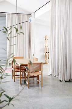 Small dining area in a large room in natural colors. Great white curtains!