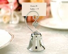 Possible wedding favor and name card holder.the bells signal a kiss for the bride and groom, kinda like the spoon against the glass cup. Charming Silver Bell with Dangling Heart Charm (Set of - - Place Card Holders Gold Wedding Favors, Elegant Wedding Favors, Bridal Shower Favors, Wedding Gifts, Wedding Bells, Wedding Souvenir, Party Favors, Wedding Ideas, Wedding Table