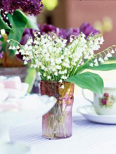 Lilly of the Valley in Colored Tumbler ~ Repurposed Tableware  Raid your antique stash for a colored drinking glass to plop a handful of flowers in for a two-second arrangement. Or fake it with an inexpensive plastic tumbler from a discount store.