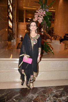 PHOTO CREDIT: Abu Jani & Sandeep Khosla  Nita Ambani attended the Pink Filly event in Mumbai dressed in Abu Jani  Sandeep Khosla. The black georgette suit featured gota embroidery with  floral motifs. Mrs. Ambani finished the look with a pink exotic leather  clutch and gold YSL tributes. Nicely done!!