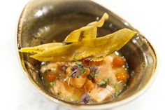 AMAZONIAN CEVICHE. Cubes of fresh Ōra King salmon -- tossed in a refreshing marinade (composed of just-squeezed lime, lemon and orange juices, pureed shallots and bird's eye chilies, touch of local honey.) Served chilled and garnished with plantain chips and baby shisho.